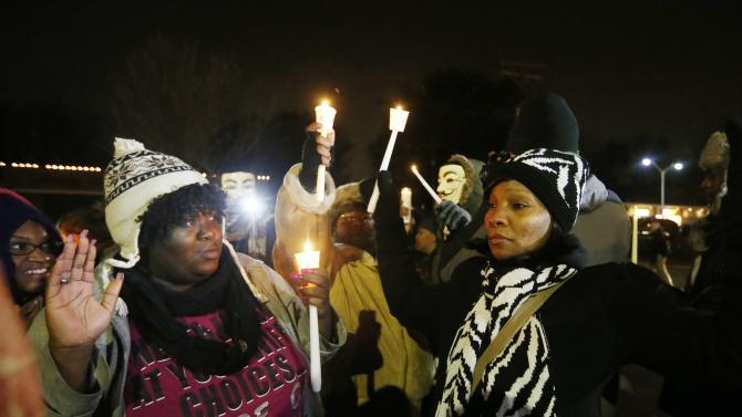 Protesters hold up their hands during a candle light vigil, protesting over the August 9 police shooting of Michael Brown, outside the Ferguson Police Department in Ferguson