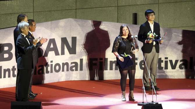 """Director Maryam Najafi, second from right, speaks after being awarded the New Currents prize during the Busan International Film Festival in Busan, South Korea, Saturday, Oct. 13, 2012. Najafi, who holds a dual citizenship in Iran and Canada, said her award-winning movie """"Kayan"""" about a Lebanese single mother in Canada depicts women's universal struggles. (AP Photo/Yonhap, Jo Jung-ho) KOREA OUT"""