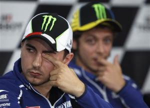 Yamaha MotoGP rider Lorenzo of Spain rubs his eye as his teammate Rossi of Italy watches during the post-qualifying news conference ahead of the Australian Motorcycle Grand Prix, at Phillip Island Circuit