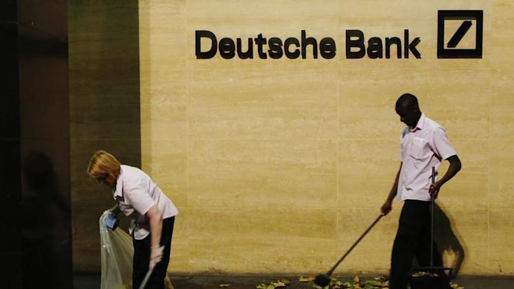 Workers sweep leaves outside Deutsche Bank offices in London