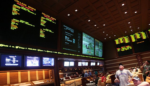FILE - Sports bettors watch the screens in the race and sports book at Wynn Las Vegas, in this March 15, 2009 file photo taken in Las Vegas. Las Vegas casinos think this weekend's NFL week three 2012 games will be the highest-scoring ever _ and that you can thank the league's replacement officials. Oddmakers say casinos are changing their expectations as interim referees add new variables to the game, changing its pace and approaches from players and coaches. (AP Photo/Isaac Brekken)