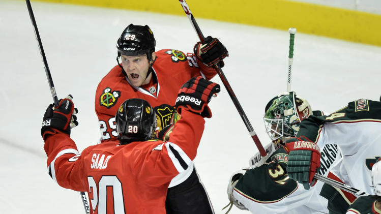 Chicago Blackhawks wingers Bryan Bickell (29) and Brandon Saad, left, celebrate after Bickell scored past Minnesota Wild goalie Niklas Backstrom of Finland, left, during the first period of an NHL hockey game, Tuesday, March 5, 2013 in Chicago.  (AP Photo/Brian Kersey)