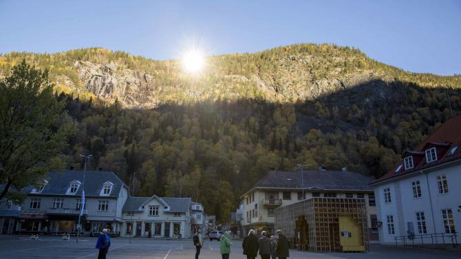 People gather in front of the town hall, where sunlight is reflected by giant mirrors erected on the mountainside, in Rjukan