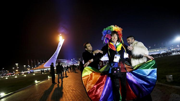 Vladimir Luxuria, center, a former Communist lawmaker in the Italian parliament and prominent crusader for transgender rights, is led away by friends to attend a women's ice hockey match after posing for photos on the Olympic Plaza at the 2014 Winter Olympics, Monday, Feb. 17, 2014, in Sochi, Russia. Luxuria was soon after detained by police upon entering the Shayba Arena