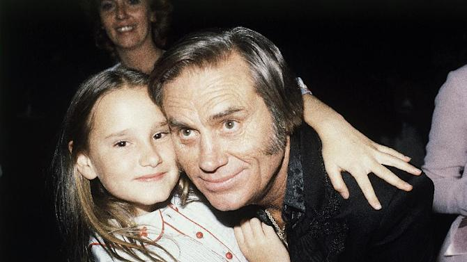 "FILE - In this April 30, 1981 file photo, Country singer George Jones, winner of top male vocalist award at the Academy of Country Music Awards, poses with his daughter Georgette, in Los Angeles, Calif.   Jones, the peerless, hard-living country singer who recorded dozens of hits about good times and regrets and peaked with the heartbreaking classic ""He Stopped Loving Her Today,"" has died. He was 81. Jones died Friday, April 26, 2013 at Vanderbilt University Medical Center in Nashville after being hospitalized with fever and irregular blood pressure, according to his publicist Kirt Webster.(AP Photo/Nick Ut, file)"