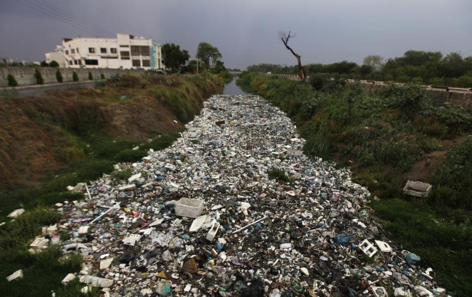 A water canal is choked by non-bio-degradable garbage in Amritsar, India, Sunday, April 22, 2012.  April 22 is observed as Earth Day every year as a tool to raise ecological awareness. (AP Photo/Altaf Qadri)