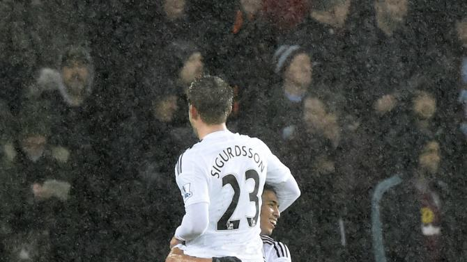 Swansea City's Gylfi Sigurdsson is lifted off the ground by Jefferson Montero after scoring a goal during their English Premier League soccer match at the Liberty Stadium in Swansea