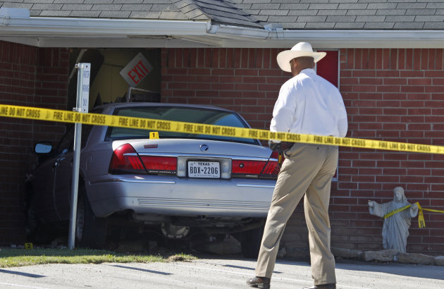 An investigator looks over a car that was crashed into the Greater Sweethome Missionary Baptist Church in Forest Hill, Texas, Monday, Oct. 29, 2012. Forest Hill Police Chief Dan Dennis says the pastor of the church is dead after the driver of the car crashed into the building and began to assault him. Dennis said officers arrived Monday afternoon at the Greater Sweethome Missionary Baptist Church to find an assault in progress. Dennis says the suspected attacker also later died shortly after being detained. (AP Photo/LM Otero)