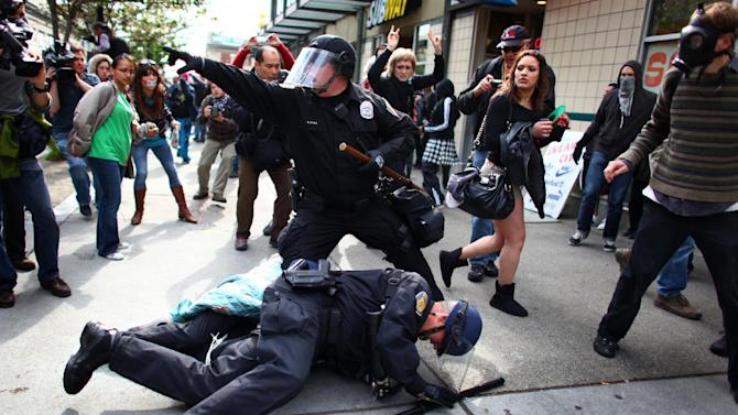 Seattle Police officers arrest a man that threw a glass jar and hit an officer in his face shield during a May Day rally on Tuesday, May 1, 2012 in downtown Seattle. The rally turned violent when black-clad protesters smashed windows and threw objects at police. (AP Photo/seattlepi.com, Joshua Trujillo) MAGS OUT; NO SALES; SEATTLE TIMES OUT; MANDATORY CREDIT; TV OUT