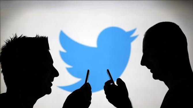 Men are silhouetted against a video screen with a Twitter logo as he poses with a Samsung S4 smartphone in this photo illustration taken in the central Bosnian town of Zenica