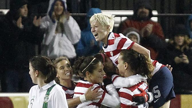 United States midfielder Megan Rapinoe, right, leaps atop teammates after their first goal during the first half of their exhibition soccer match against Ireland in Portland, Ore., Wednesday, Nov. 28, 2012. Ireland midfielder Niamh Fahey, left, walks away. (AP Photo/Don Ryan)