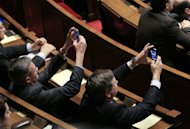 French MPs take pictures with their mobile phones at the National Assembly in March. The worldwide mobile phone market is expected to grow this year at its slowest pace since 2009, hurt by sluggish economic conditions, a survey showed Wednesday