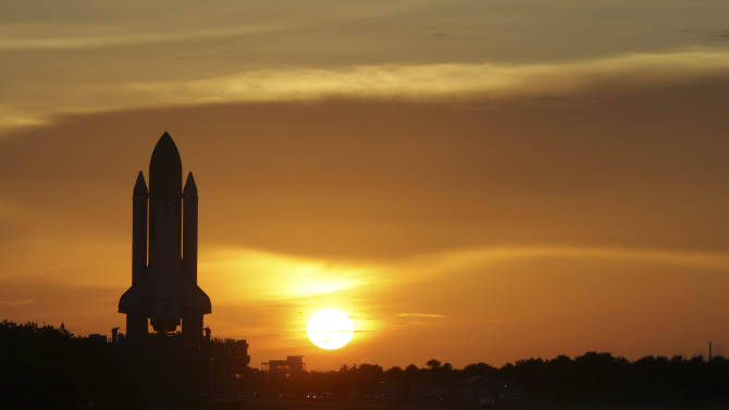 FILE - In this Tuesday, Aug. 4, 2009 file photo, Space shuttle Discovery moves along it's path at sunrise to pad 39A at the Kennedy Space Center in Cape Cananveral, Fla. The space shuttle was sold to America as cheap, safe and reliable. It was none of those. It cost tens of billions of dollars, ended the lives of 14 astronauts and managed to make fewer half the flights promised. Yet despite all that, there were monumental achievements that in the beginning were unforeseen: major scientific advances, stunning photos of the cosmos, a high-flying vehicle of diplomacy that helped bring Cold War enemies closer, and something to brag about. (AP Photo/John Raoux, File)