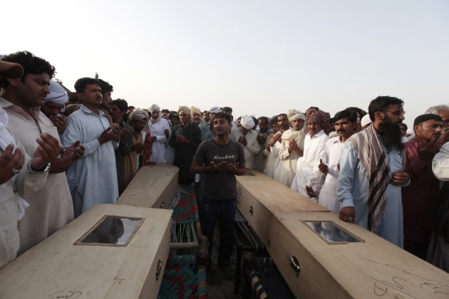 People pray over coffins of children who died after a gas cylinder exploded on a school bus, during their funeral on the outskirts of Gujrat
