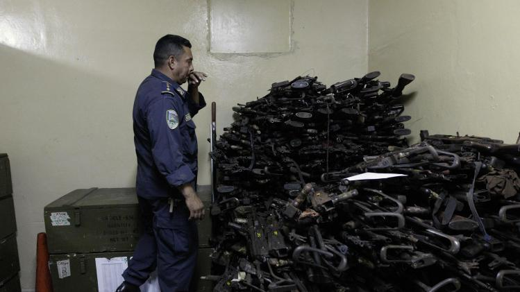 A police officer looks towards weapons that are to be destroyed at the police headquarters in Tegucigalpa