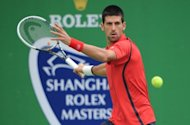 Novak Djokovic of Serbia hits a return against Grigor Dimitrov of Bulgaria in their second round match of the Shanghai Masters tennis tournament in Shanghai. History-making Kei Nishikori was dumped out of the Shanghai Masters as Djokovic cruised into the third round and defending champion Andy Murray was handed a walkover