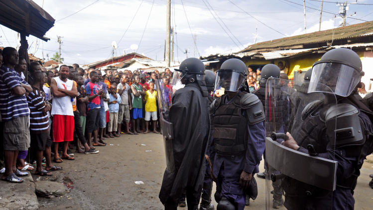 Liberian security officers dressed in riot gear, right, control a crowed of people in the West Point area, as the government clamps down on the movement of people to prevent the spread of the Ebola virus in Monrovia, Liberia, Wednesday, Aug. 20, 2014. Security forces deployed Wednesday to enforce a quarantine around a slum in the Liberian capital, stepping up the government's fight to stop the spread of Ebola and unnerving residents. (AP Photo/Abbas Dulleh)