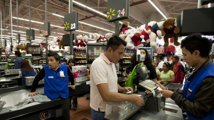 FILE - In this Nov. 18, 2011 file photo, a man pays at the cash register at a Wal-Mart Superstore in Mexico City. Lawmakers are making public emails that show that Wal-Mart Stores Inc.'s CEO found out in 2005 that the retailer was handing out bribes in Mexico. (AP Photo)