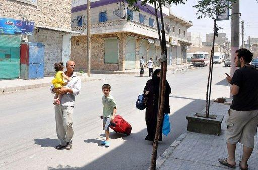 A Syrian family walks past shuttered shops as they flee the Shaar neighborhood of the restive city of Aleppo