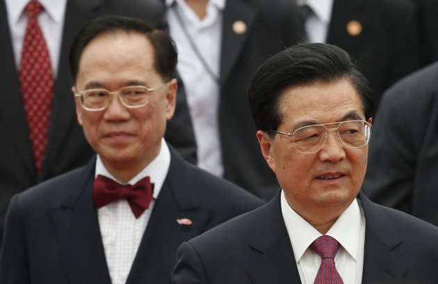 Chinese President Hu Jintao is accompanied by Hong Kong Chief Executive Donald Tsang, left, after arriving at Hong Kong international airport Friday, June 29, 2012. Hu is in Hong Kong to install a new but already unpopular governor of the semiautonomous Chinese territory. (AP Photo/Kin Cheung)