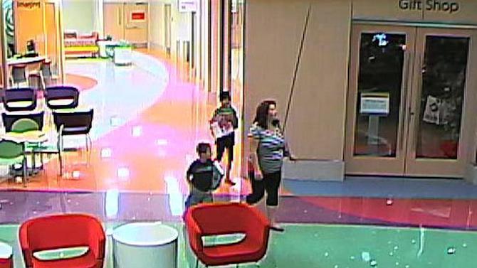 In this hospital surveillance photo released by the Phoenix Police Department on Dec. 3, 2012, a woman is seen with her 11-year-old daughter, a leukemia patient who had her arm amputated and a heart catheter inserted due to an infection. Authorities say the woman inexplicably took the girl from the hospital last week. Police say that if the catheter is left in too long it could lead to a deadly infection. The family's identity is being withheld but they are calling the girl Emily. (AP Photo/Phoenix Police Department)