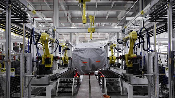 A covered vehicle sits in part of the new paint shop at Chrysler's Sterling Heights Assembly Plant in Sterling Heights, Mich.,Tuesday, July 16, 2013. Chrysler will start selling a completely new midsize car during the first quarter of next year, company executives confirmed on Tuesday. The replacement for the aging Chrysler 200 and Dodge Avenger is badly needed for the company to compete in the most popular part of the U.S. auto market. Chrysler officials gave few details about the new car. It will be built at a factory in Sterling Heights, north of Detroit, where the 200 and Avenger are now built. (AP Photo/Paul Sancya)