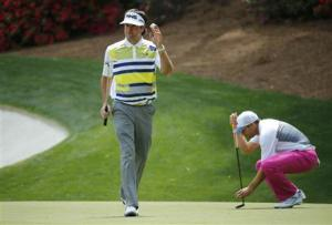 U.S. golfer Bubba Watson waves after making a birdie on the 13th hole as Spain's Sergio Garcia places his ball during the second round of the Masters golf tournament at the Augusta National Golf Club in Augusta