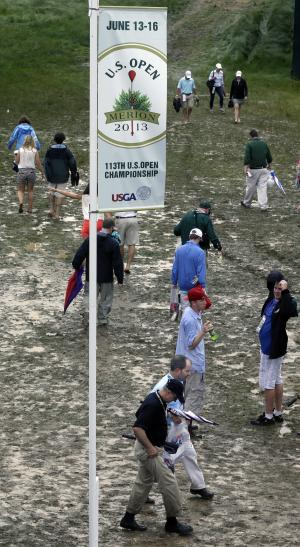 Spectators make their way down a muddy path during practice for the U.S. Open golf tournament at Merion Golf Club, Monday, June 10, 2013, in Ardmore, Pa. (AP Photo/Gene J. Puskar)