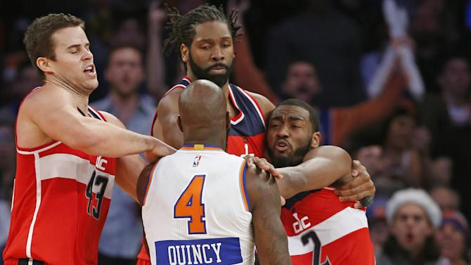 Washington Wizards forwards Kris Humphries, left, and Nene Hilario restrain New York Knicks forward Quincy Acy (4) and Wizards guard John Wall (2) after they engaged in an on-court scuffle in the second half of an NBA basketball game at Madison Square Garden in New York, Thursday, Dec. 25, 2014. The Wizards defeated the Knicks 102-91. Acy was ejected from the game Wall received a technical foul. (AP Photo/Kathy Willens)