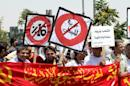 "FILE - In this June 24, 2011 file photo, supporters of the Communist Party hold banners demanding cancellation of the sales tax during a demonstration by opposition parties demanding an end to government corruption in front of the prime minister's office in Amman, Jordan. White placard on right reads, ""People want the stolen money back."" A new report by an anti-corruption watchdog reveals that nearly 30 percent of people in the Middle East have had to pay a bribe to access some kind of public service and that courts had the worst bribery rate of six services asked about. (AP Photo/ Nader Daoud, File)"