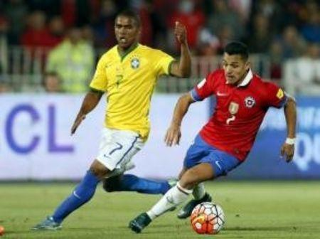 Sanchez controls for the ball past Costa of Brazil during their 2018 World Cup qualifying soccer match in Santiago