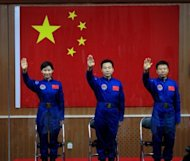 Chinese first woman astronaut Liu Yang together with her two male colleagues, Jing Haipeng (centre) and Liu Wang wave as they are introduced during a press conference at the Jiuquan space base in Gansu province. China launched its most ambitious space mission to date, sending its first female astronaut to the final frontier and bidding to achieve the country&#39;s first manual space docking