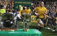 Australian lock Nathan Sharpe runs past the Nelson Mandela trophy ahead of the Rugby Championship Test against South Africa on September 8. Sharpe took over the captaincy for the dying minutes against the Springboks on Saturday