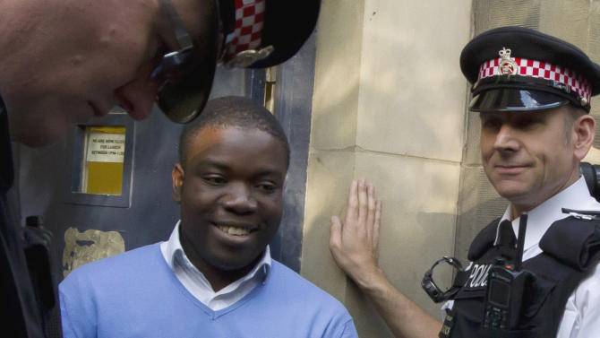 FILE This Friday, Sept. 16, 2011 file photo shows former UBS trader Kweku Adoboli, center, walking to a security van flanked by police officers after appearing at the City of London Magistrates Court in London.  A rogue trader who lost $2.2 billion in bad deals at Swiss bank UBS was convicted of fraud on Tuesday, Nov. 20, 2012. Ghanaian-born Kweku Adoboli, 32, exceeded his trading limits and failed to hedge trades, allegedly faking records to cover his tracks at the bank's London office. At one point, Adoboli risked running losses of up to $12 billion. The fraud conviction carries a maximum jail term of 10 years. (AP Photo/Matt Dunham, File)