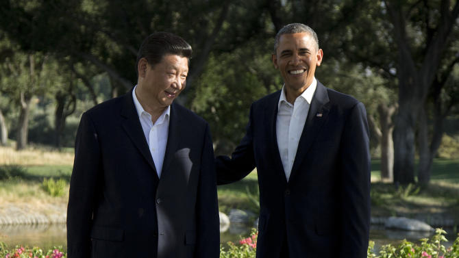 President Barack Obama poses with Chinese President Xi Jinping at the Annenberg Retreat at Sunnylands as they meet for talks Friday, June 7, 2013, in Rancho Mirage, Calif. Seeking a fresh start to a complex relationship, the two leaders are retreating to the sprawling desert estate for two days of talks on high-stakes issues, including cybersecurity and North Korea's nuclear threats. (AP Photo/Evan Vucci)