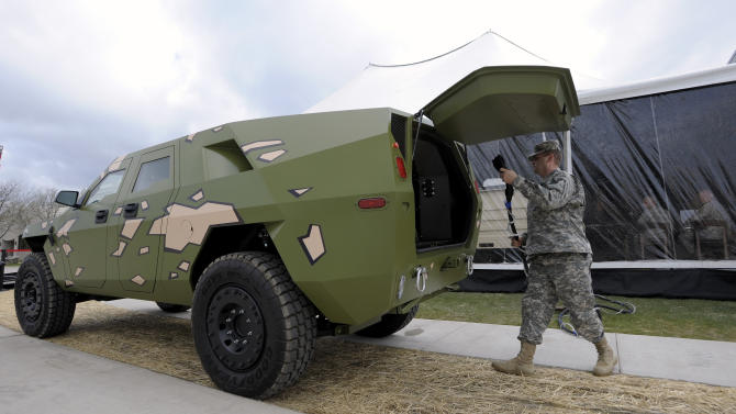 """Captain Robert Shaw plugs a cord into this Fuel Efficient Demonstrator vehicle (FED) named, """"BRAVO"""" to power electronics in the grand-opening tent, Wednesday, April 11, 2012 in Warren, Mich. The U.S. Army unveiled a new laboratory Wednesday that can simulate Afghanistan's desert heat and Antarctica's extreme cold in an effort to discover how to save energy and make combat vehicles fuel-efficient. (AP Photo/Detroit News, Todd McInturf )  DETROIT FREE PRESS OUT; HUFFINGTON POST OUT"""