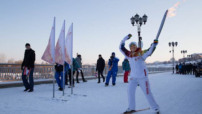 In this photo provided by Olympictorch2014.com torch bearer Luisa Noskova skis with an Olympic torch on the embankment of the Tura River during the Olympic torch relay in Tyumen, western Siberia, Russia, Wednesday, Dec. 11, 2013. The 65,000-kilometer (40,389 mile) Sochi torch relay, which started on Oct. 7, is the longest in Olympic history. The torch has traveled to the North Pole on a Russian nuclear-powered icebreaker and has even been flown into space. (AP Photo/Olympictorch2014.com)