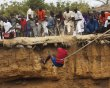 A man ascends by bungee cords from a large former well during a traditional ceremony in the village of Ndande