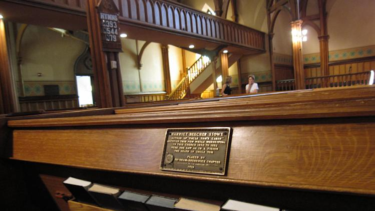 "This July 13, 2012 photo shows the marker on a pew at First Parish Church in Brunswick, Maine, where ""Uncle Tom's Cabin"" author Harriet Beecher Stowe sat in 1851 when she had a vision of a scene for the book. The church, a Gothic Revival building that dates to the 1840s, is one of 14 sites in Brunswick on the National Register of Historic Places. (AP Photo/Beth Harpaz)"