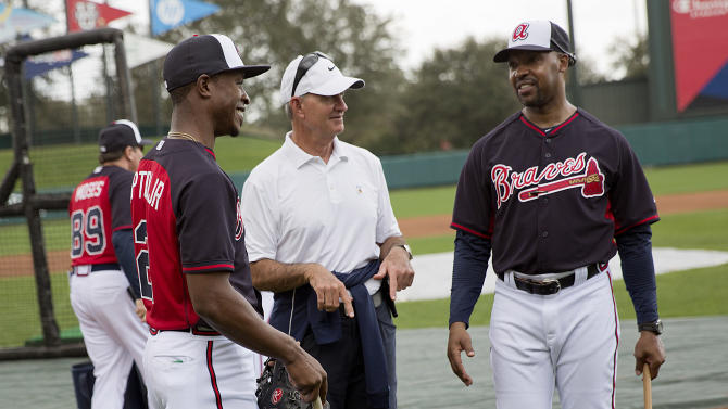 Atlanta Braves' Melvin Upton Jr., left, wearing a jersey with his new name after having it changed on the Braves' roster from B.J. Upton to Melvin Upton Jr., talks with John Hart, president of baseball operations, center, and third base coach Bo Porter during a spring training baseball workout, Monday, Feb. 23, 2015, in Kissimmee, Fla. (AP Photo/David Goldman)