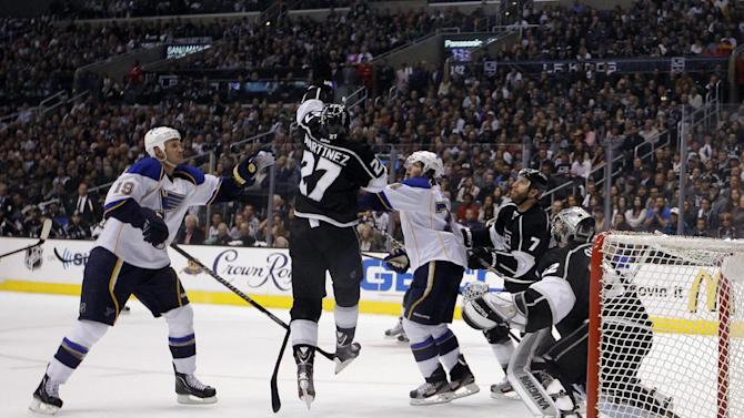 Los Angeles Kings' Alec Martinez(27) jumps to catch a puck as St. Louis Blues' Jay Bouwmeester(19) and T.J. Oshie(74) watch during the first period in Game 6 of a first-round NHL hockey Stanley Cup playoff series in Los Angeles, Friday, May 10, 2013. (AP Photo/Jae C. Hong)