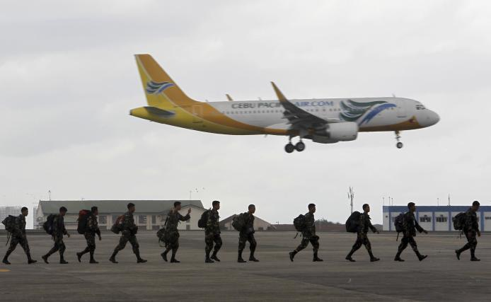 Members of Philippine Army prepare to board a US C-130 plane at Villamor Air Base
