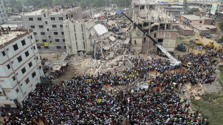 FILE - In this April 25, 2013 file photo, Bangladeshi people gather as rescuers look for survivors and victims at the site of Rana Plaza building that collapsed a day before, in Savar, near Dhaka, Bangladesh. The building collapse killed 1,129 people in the worst garment industry tragedy. Bangladeshi garment factories are routinely built without consulting engineers. Many are located in commercial or residential buildings not designed to withstand the stress of heavy manufacturing. Some add illegal extra floors atop support columns too weak to hold them, according to a survey of scores of factories by an engineering university. The textiles minister said a third inspection, conducted by the government, could show that as many as 300 factories were unsafe. (AP Photo/A.M.Ahad, File)
