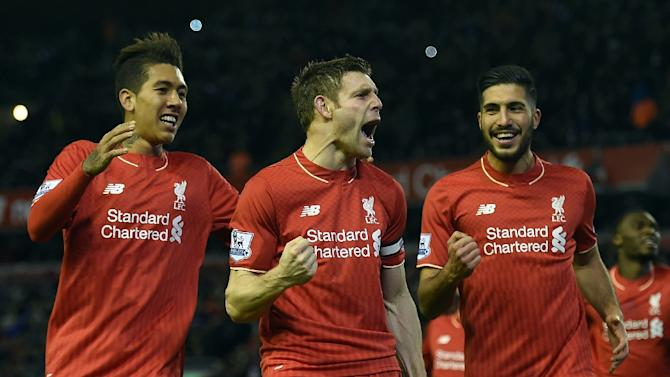 Liverpool's James Milner (C) celebrates with teammates Roberto Firmino and Emre Can (R) after scoring a goal from the penalty spot during their English Premier League match against Swansea City, at Anfield in Liverpool, on November 29, 2015