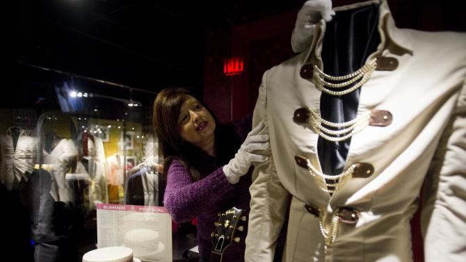 """Archivist Dee Dee Antle adjusts one of Elvis Presley's famous jumpsuits during the opening of Graceland's newest exhibition in Memphis, Tenn., March 4, 2013. """"Elvis: Live from Vegas."""" The show features footage from some of """"The King's"""" more memorable performances in Las Vegas and artifacts including Elvis's famous American Eagle jumpsuit and even a contract written on a table cloth and signed by Elvis's manager Col. Tom Parker. (AP Photo/The Commercial Appeal, Brandon Dill)"""