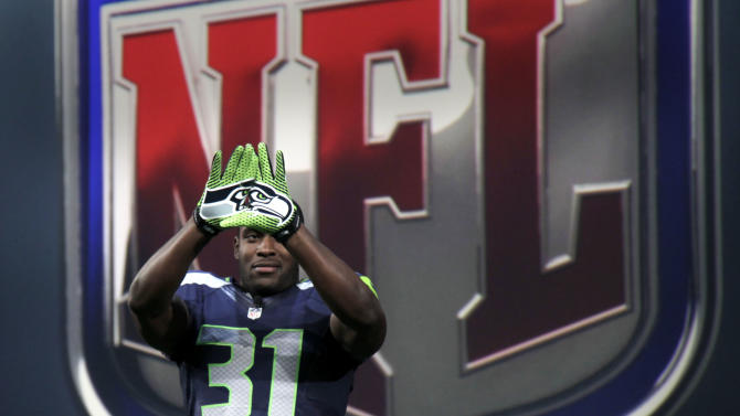 Seattle Seahawks' Kam Chancellor shows off the new design for gloves during a presentation in New York, Tuesday, April 3, 2012.  The NFL and Nike showed off the new look in grand style with a gridiron-styled fashion show at a Brooklyn film studio. (AP Photo/Seth Wenig)