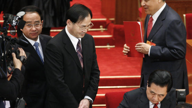 In this photo taken on March 14, 2010, Ling Jihua, a loyal aide and confidante to President Hu Jintao, left, looks on as Chinese President Hu Jintao, bottom right, signs a document after attending the closing ceremony of the National People's Congress at the Great Hall of the People in Beijing. China's hopes for a smooth, once-a-decade political transition have been shaken by a lurid new scandal involving the death of Ling's son, who crashed during what may have been sex games in a speeding Ferrari. (AP Photo/Andy Wong)