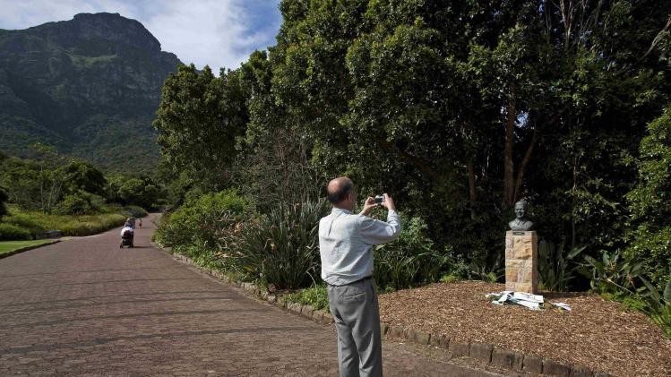 A man takes picture of tributes left at bust of former South African President Mandela in Kirstenbosch National Botanical Gardens in Cape Town