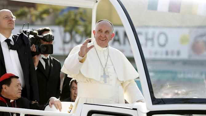 Pope Francis waves to the crowd on his way to celebrate mass at the Guadalupe's basilica in Mexico City