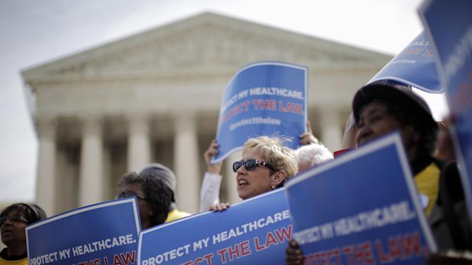 FILE - In this March 28, 2012 file photo, supporters of health care reform rally in front of the Supreme Court in Washington on the final day of arguments regarding the health care law signed by President Barack Obama. Congressional budget analysts are now estimating that nearly 6 million Americans, most of them in the middle class, will have to pay a tax penalty for not getting health insurance once Obama's health care law is fully in place. That's 2 million more than a previous estimate found, or a 50 percent increase. Starting in 2014, the new health care law requires virtually every legal resident of the U.S. to carry health insurance, or face a tax penalty. The Supreme Court upheld Obama's law as constitutional after finding that the penalty fell within the power of Congress to impose taxes.  (AP Photo/Charles Dharapak, File)